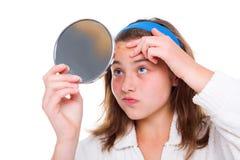 Flickan undersöker hennes finnar i spegeln Arkivbild