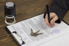 Flickan undertecknar ett avtal för köpet av fastigheten, på tabellen ligger avtalet, skyddsremsan och tangenterna till lägenheten arkivbild