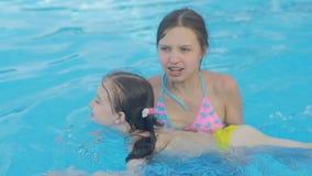 Flickan undervisar hennes mer unga syster att simma arkivfilmer