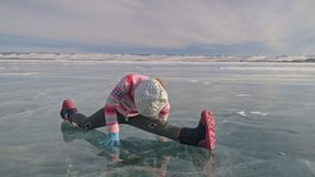 Flickan utbildar övningsyoga i vinter Barn är gör sträckning och meditation på is i natur Ungen öva yoga lager videofilmer
