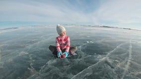 Flickan utbildar övningsyoga i vinter Barn är gör sträckning och meditation på is i natur Ungen öva yoga stock video
