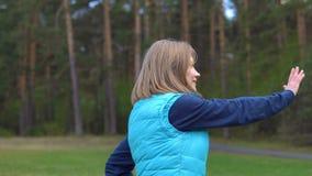 Flickan utbildar i parkera på gräsmattan stock video