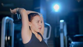 Flickan utför övningsförlängning av armar med en hantel bakifrån huvudet arkivfilmer