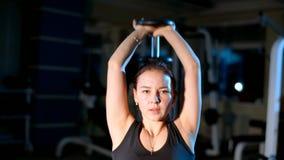Flickan utför övningsförlängning av armar med en hantel bakifrån huvudet lager videofilmer