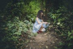 Flickan väljer blommor i skogen Arkivfoton
