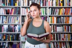 Flickan väljer en bok i arkivet royaltyfri foto