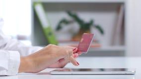 Flickan väljer en kreditkort för att göra köp online- close upp arkivfilmer