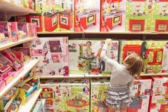 Flickan väljer en leksak i en leksak shoppar Royaltyfri Bild