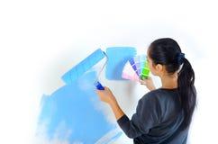 Flickan väljer färg för att måla väggar Arkivfoton
