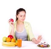Flickan väljer frukt i stället för sötsaker arkivbild