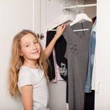 Flickan väljer kläder från garderoben Royaltyfri Fotografi