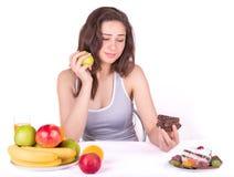 Flickan väljer mellan ett äpple och en kaka arkivbild