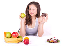 Flickan väljer mellan ett äpple och en kaka Royaltyfri Foto