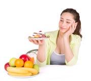 Flickan väljer mellan frukt och sötsaker arkivbild