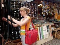 Flickan väljer piskar bältet i en herrekiperingsartiklarbänk arkivfoton