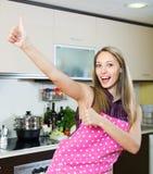 Flickan vände upp tummarna i kök Royaltyfria Bilder