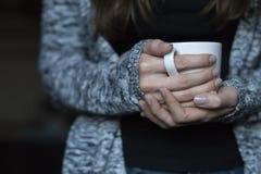 Flickan värme hennes händer på en vit kopp av varmt te royaltyfria foton