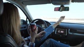 Flickan värmes av en varm drink i bilen Utanför vintern Hon kopplar av och sätter hennes fot på panelen 4K långsam mo arkivfilmer