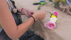 Flickan väver kransen från blommor arkivfilmer
