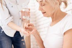 Flickan vårdar den äldre kvinnan hemma Flickan kommer med vatten och preventivpillerar royaltyfria bilder