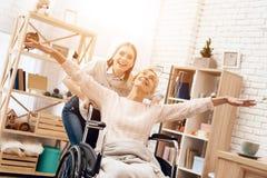 Flickan vårdar den äldre kvinnan hemma Flickan rider kvinnan i rullstol Kvinnan känner sig som flyg Royaltyfria Bilder