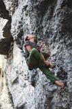 Flickan vaggar klättraren som vilar, medan klättra på klippan Royaltyfri Foto