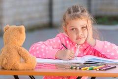 Flickan vet inte hur man fortsätter för att dra teckningsblyertspennor Arkivbild