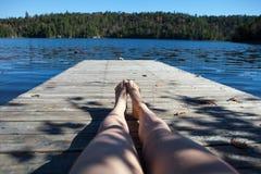Flickan vilar på pir Sjö i nedgångskogen, Kanada royaltyfria foton