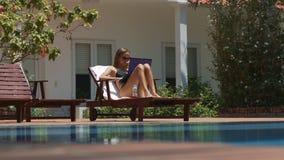 Flickan vilar på trästol surfar internet vid pölen arkivfilmer