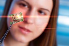 Flickan visar den nya mikrochipens Royaltyfri Foto