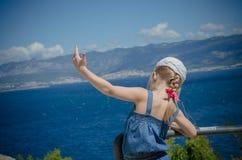 Flickan visar en fågel med en havssikt Royaltyfri Bild