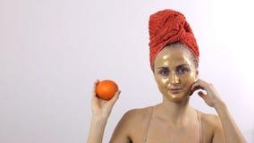 Flickan visar en guld- maskering på hennes framsida som jämförs till en orange frukt lager videofilmer