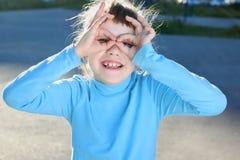 Flickan visar exponeringsglas på lekplats på sommar Arkivbild