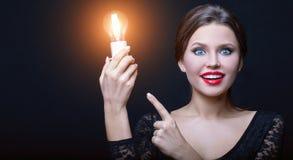 Flickan visar hennes finger på den glödande kulan i hennes hand arkivbilder