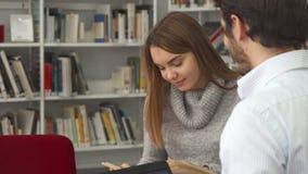 Flickan visar något i boken till hennes klasskompis lager videofilmer