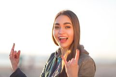 Flickan visar tecknet av hornen Royaltyfri Foto