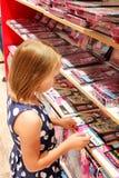 Flickan väljer en bok i en bokhandel Arkivfoton