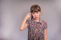 Flickan vrider ett finger på en tempel Arkivbild