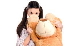 Flickanederlag bak det stora teddybear. Arkivbild