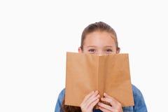 Flickanederlag henne framsida bak en bok Royaltyfri Foto