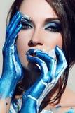 Flickans framsida med blå makeup Arkivbild