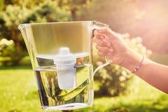 Flickans hand rymmer en tillbringare för vattenfilter exponerad av solstrålar i en solig sommarträdgård i en varm dag arkivfoton