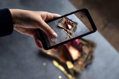 Flickans hand skjuter matefterrätten på telefonen kakan för chokladpudding fyllde med nya bär på det guld- magasinet med folk och royaltyfri foto