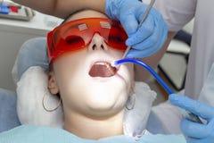 Flickapatient på mottagandet på tandläkarebehandling av den carious tanden flickan ligger på den tand- stolen med hans öppna mun  royaltyfri foto