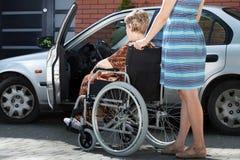 Flickaportionkvinna på rullstolen som får in i en bil Royaltyfri Foto