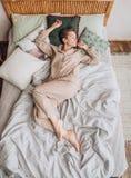 Flickapyjamas som sover ljus för sängdekorjul arkivbild