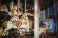 Flickaridning på en vit häst på en karusell Arkivfoto