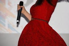 Flickasångaren i en ljus röd klänning rymmer en mikrofon i hennes hand och virvlar arkivbild