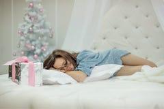 Flickasömnar i en vitrundasäng nära en kudde står en julgåva i sovrummet med ett träd för nytt år royaltyfria bilder