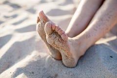 Flickas fot på sand Arkivbild